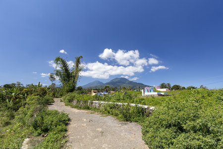 Road leading past a catholic cemetery and Poco Mandasawu mountain in the distance in Flores, Indonesia. 免版税图像