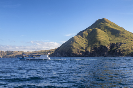 Blue ocean and a single hill on Pulau Padar Island in the Komodo National Park. 免版税图像