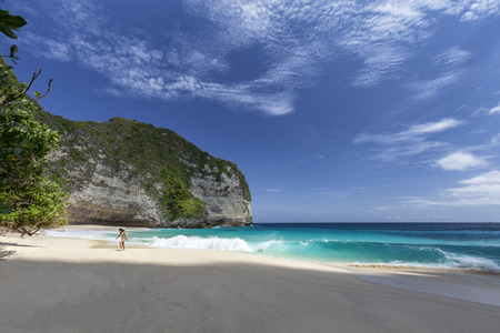 Small waves crash on the shore at Kelingking beach on Nusa Penida in Indonesia.