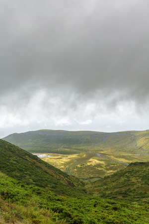 Portrait view of a hill leading down to Caldeira Branca on Flores Island in Portugal.