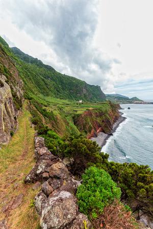 A portrait view of a hiking trail near Ponta da Faja village on Flores island in the Azores.