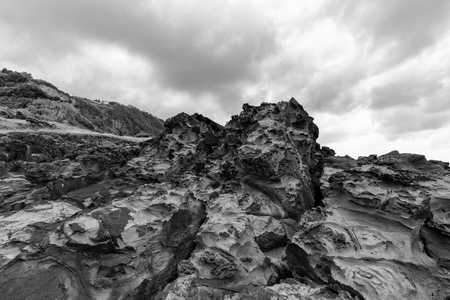 Black and white view of dramatic clouds and volcanic rocks in Flores, Azores. Imagens
