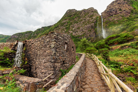 Stone path leading to the Cascata do Poco do Bacalhau waterfall with a rock building in the foreground.