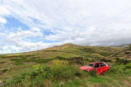 An abandoned red car on the side of the road in rural Flores, Azores.