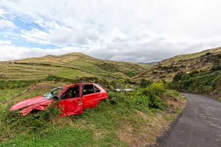 An abandoned smashed red car on the side of the road in rural Flores, Portugal. Stok Fotoğraf