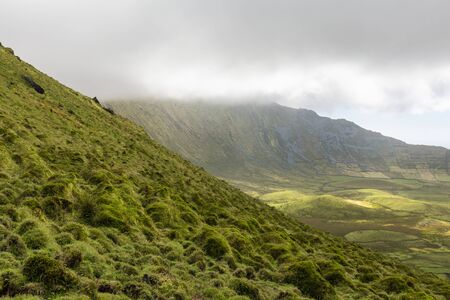 Sloping green pasture and grazing land in the Corvo caldera on the island of Corvo in the Azores, Portugal.