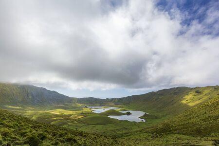 Beautiful parting clouds over the massive Corvo Caldera on the island of Corvo in the Azores, Portugal.