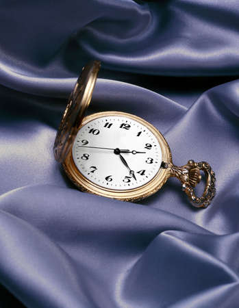 Gold pocket watch on satin photo