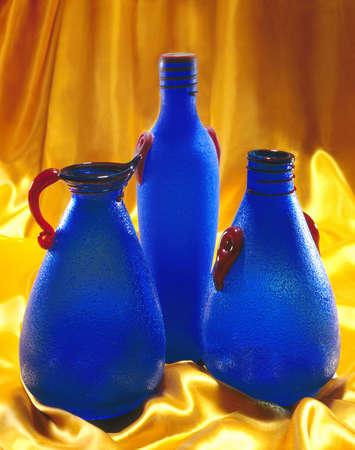 furnishings: Blue glass bottles on gold satin