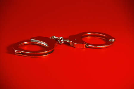 pair of handcuffs on a red background photo
