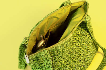 Green purse with cell phone on yellow background.