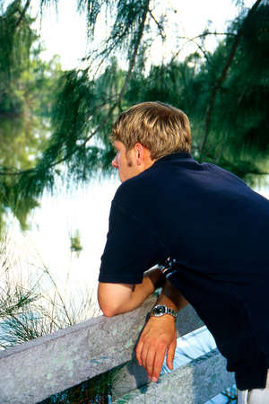 Young man thinking while looking over water