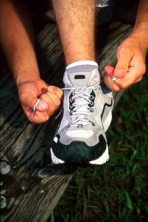 Man tieing athletic shoe Stock Photo