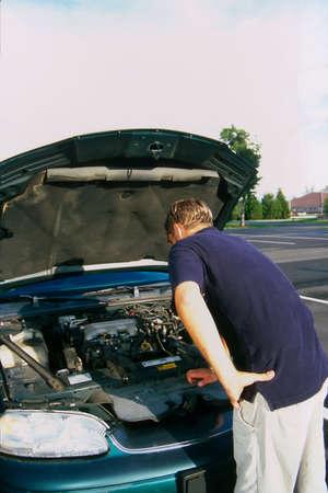 Man buiten kijken onder motorkap van auto Stockfoto