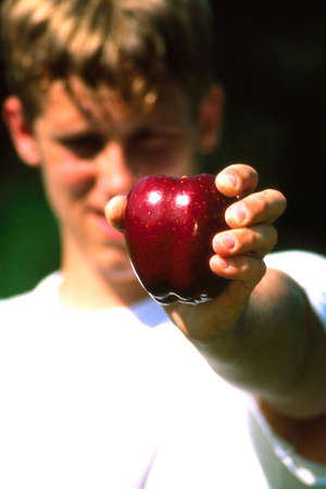 Man holding apple out with face out of focus and apple in focus