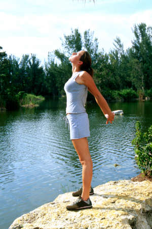 full strenght: Girl stretching outside on a rock Stock Photo