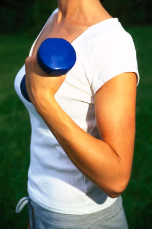 Woman curling a dumbbell Stock Photo