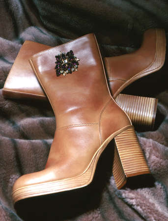 broach: Pair of boots laying on fur with broach