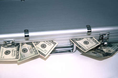 Sliver briefcase with money spilling out photo