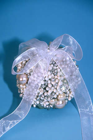 Blue and white beaded Christmas ornament on a teal background 写真素材