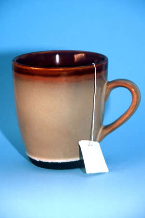 steam mouth: Brown mug with tea tag hanging off the side on a teal background
