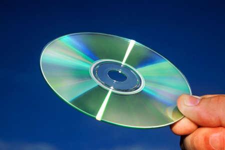 Hand holding cd against a blue sky photo