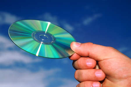 Hand holding a cd against a blue sky Stock Photo