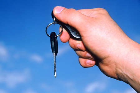Hand holding car key against a blue sky Stock Photo