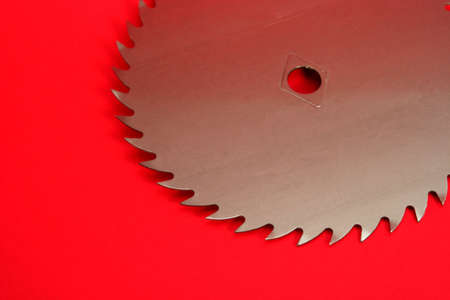 build buzz: Part of a circular saw on a red background Stock Photo