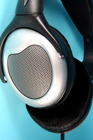 earpiece: Earpiece of a pair of headphones on  a blue background