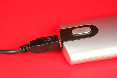 Silver memory card reader on a red background