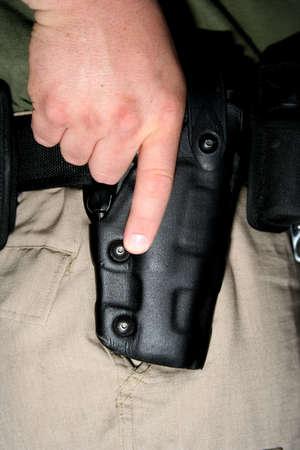 holster: Cop con pistola en mano en funda  Foto de archivo