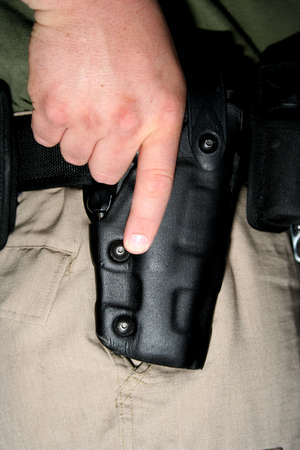 enforce:  Cop with hand on gun in holster