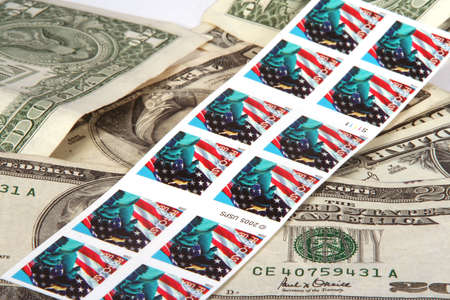 Book of stamps on pile of money Stock Photo