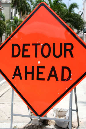 mislead: Orange detour sign in road