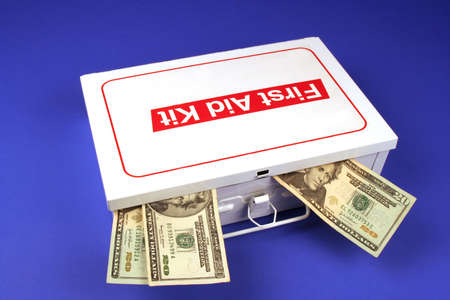 First aid kit on a blue background with three twenty dollar bills sticking out of it Stock Photo