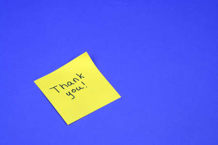 Thank you written on a yellow sticky note on a blue background