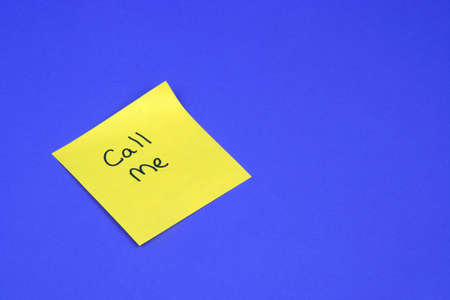 Call Me written on a yellow sticky note on a blue background photo