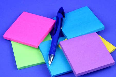 notas adhesivas: Colorido notas adhesivas sobre fondo azul con una pluma  Foto de archivo