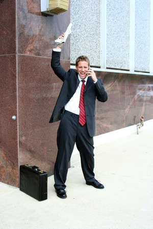 Man in suit holding stock pages on cell phone with a happy expression photo