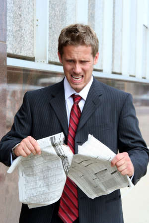 Business man looking angry tearing the stock pages of a newspaper Archivio Fotografico