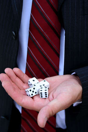 Closeup of dice in hand of man wearing suit photo