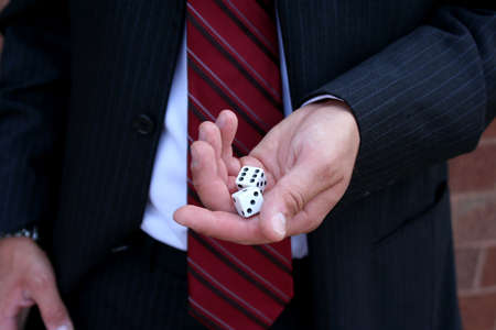Closeup of dice in hand of man wearing suit
