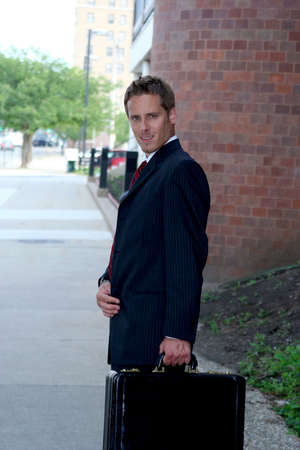 Business man holding a briefcase and smiling photo