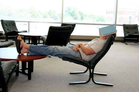 Student in library sleeping with book over face Stock Photo - 540685
