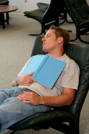 Student sleeping with book over chest