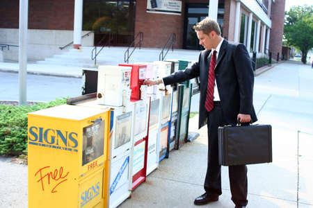 Man in suit selecting newspaper from stand Stock Photo