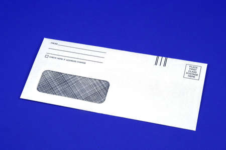 postmaster: Blank business envelope on a blue background Stock Photo