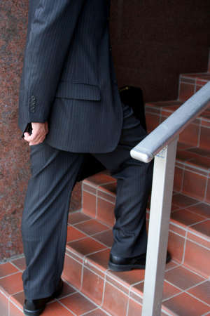 Businessman climbing stairs showing lower half of body photo