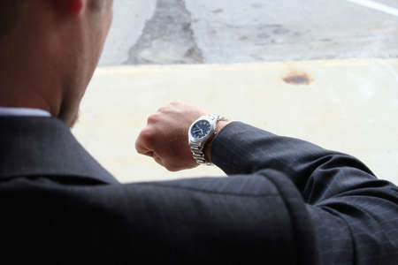 Businessman checking watch shot from over shoulder photo